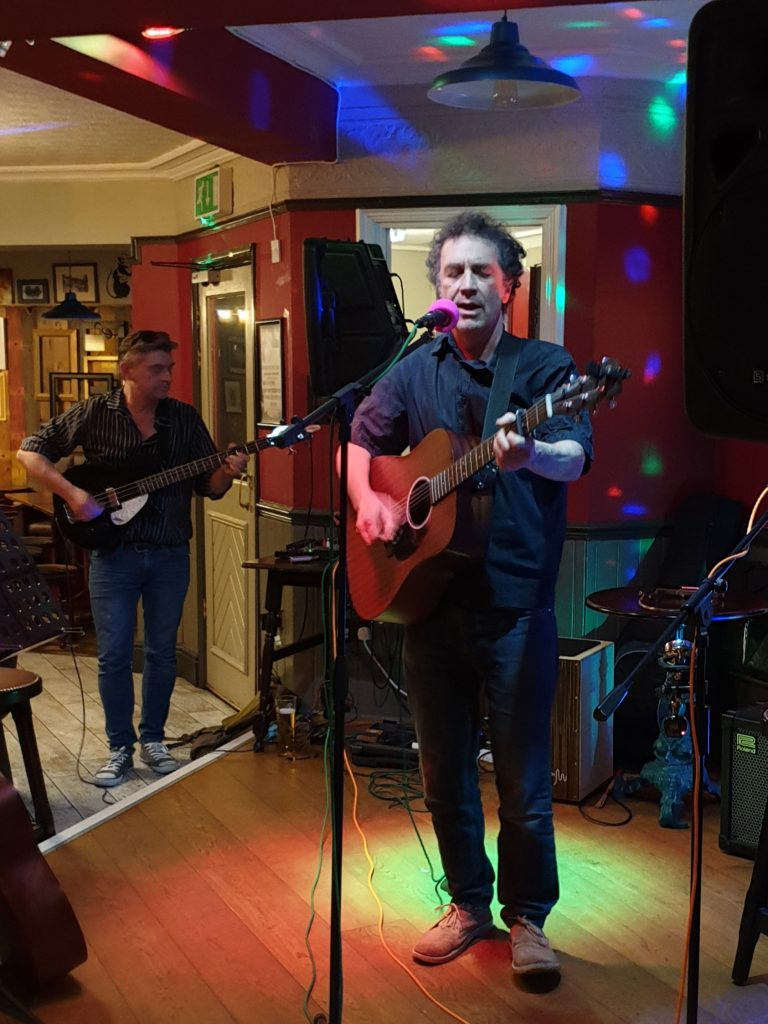 Shem Sharples playing guitar and singing live at the Chi open mic on Monday 29th April 2019.